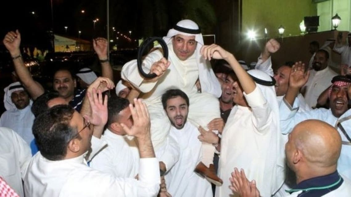 Poll candidate Jamal al-Omar (C) celebrates with supporters following parliamentary elections, in Kuwait City, on July 28, 2013.