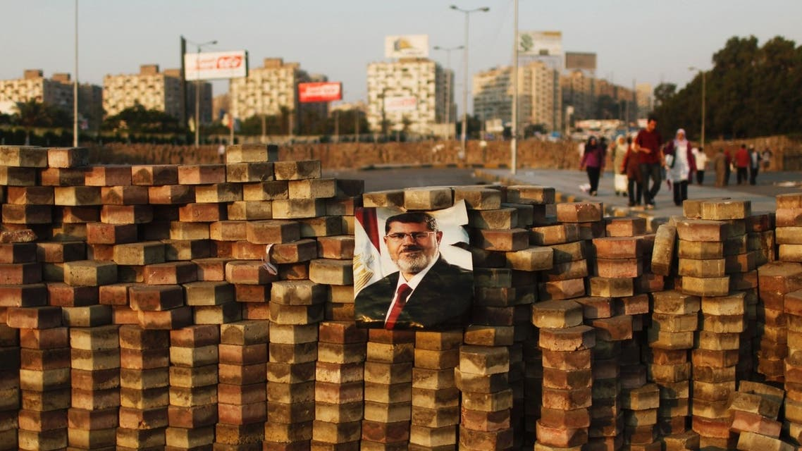 Supporters of deposed Egyptian President Mohamed Mursi (depicted in poster) walk behind a makeshift barrier built to demarcate their sit-in area around Raba' al-Adawya mosque, east of Cairo, August 3, 2013.