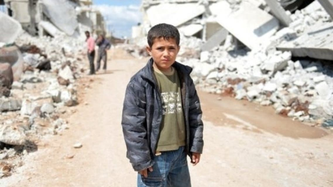 A young Syrian boy poses for a picture between destroyed houses in the northern Syrian town of Azaz on April 21, 2013. (File photo: AFP)