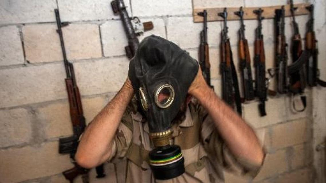 A Syrian rebel tries on a gas mask seized from a Syrian army factory in the northwestern province of Idlib on 18 July 2013. (Photo: AFP