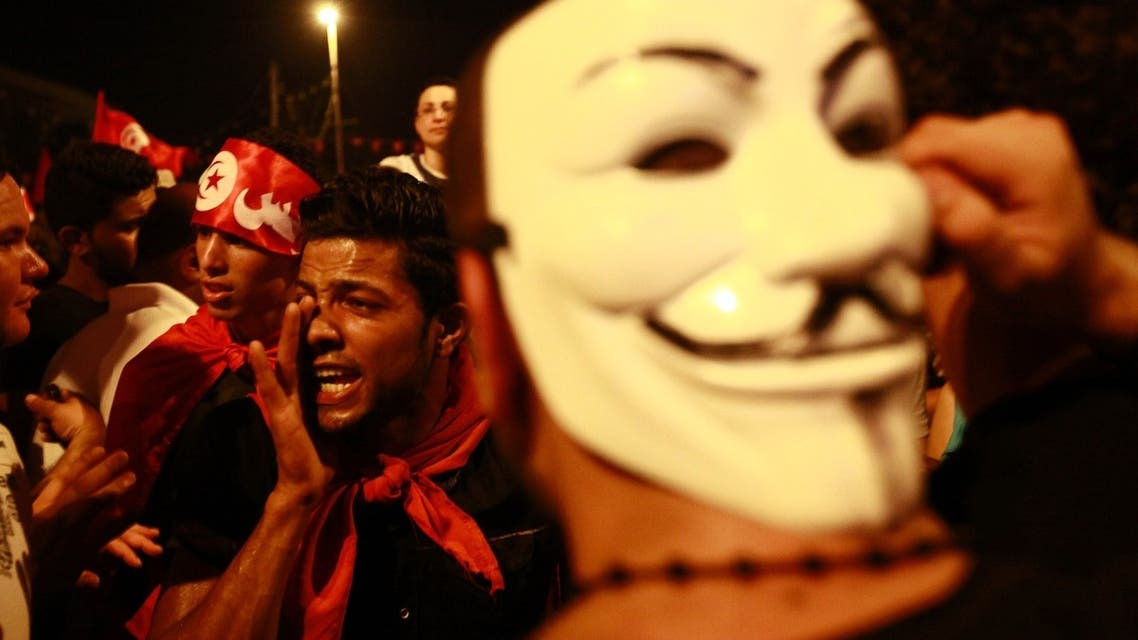 An anti-government protester wears a Guy Fawkes mask as another shouts slogans during a demonstration in Tunis August 6, 2013.