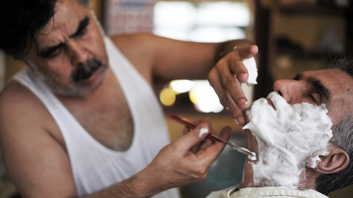 A Turkish barber Mehmet Haskan (R) cuts a client's hair at his salon at Tarlabasi on July 19, 2013 in Istanbul. (AFP)