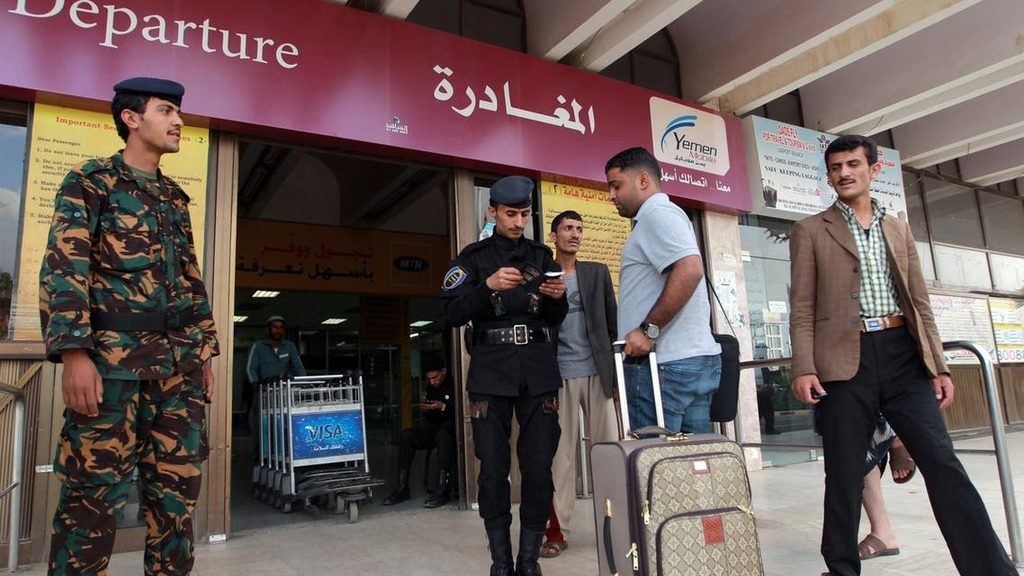 People present their documents before entering the departure lounge at Sanaa International Airport to leave Yemen on August 6, 2013.