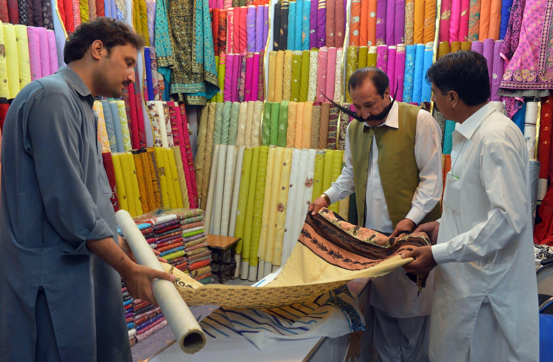Pakistani businessman Malik Amir Mohammad Khan Afridi (2nd R) buys cloth at a market in Peshawar. (AFP)