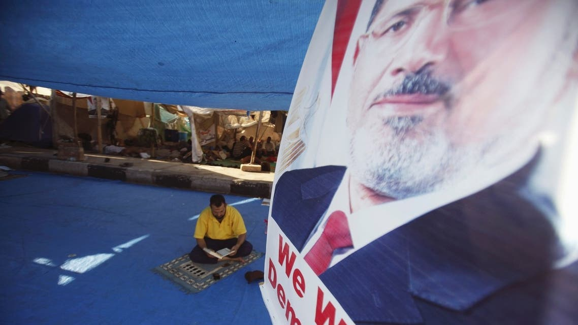 A poster of deposed Egyptian President Mohamed Mursi is seen, as a member of the Muslim Brotherhood and supporter of Mursi reads the Koran in his tent at Rabaa Adawiya Square
