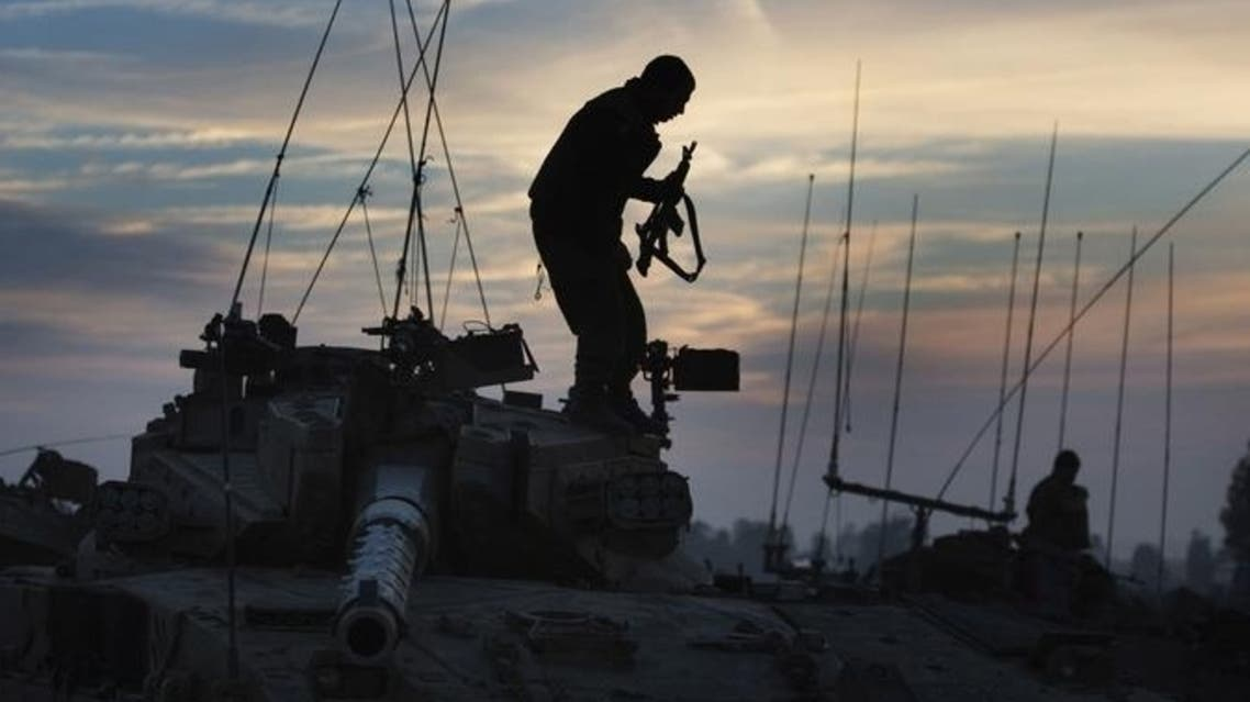 An Israeli soldiers stands on his tank at an army staging area on Nov. 21 near the Israel-Gaza Strip border.