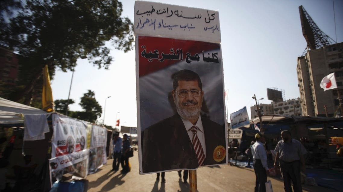 A poster of deposed Egyptian President Mohamed Mursi is seen as members of the Muslim Brotherhood and supporters of Mursi walk at the Rabaa Adawiya Square