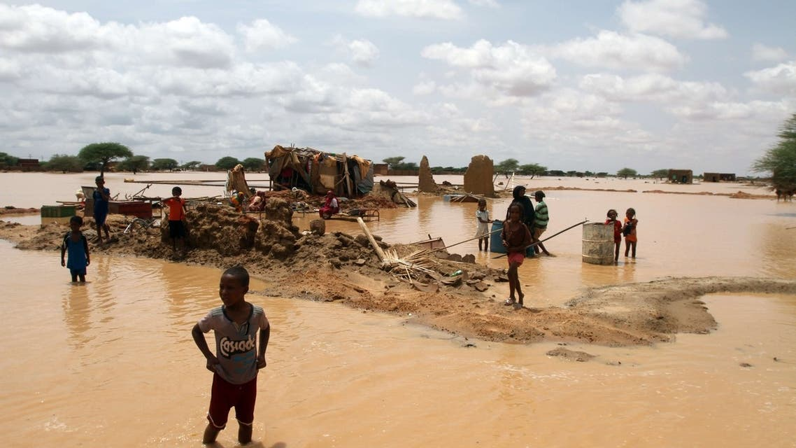 Sudanese children walks through a flooded street next to their home on the outskirts of the capital Khartoum on August 10, 2013. AFP
