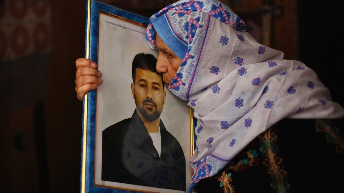 The mother of Palestinian Salah al-Shaer, who  has been held by Israel for 20 years, kisses his picture after hearing news on the expected release of her son on August 12, 2013. (Reuters)