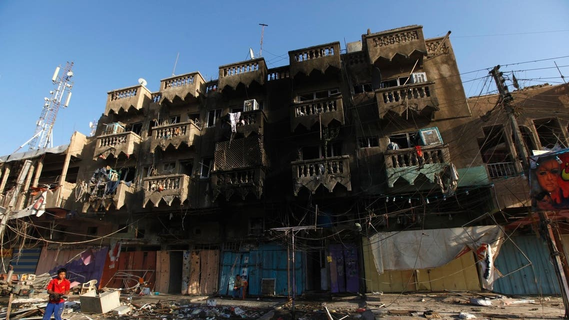A boy looks at the site of a car bomb attack in the Shaab neighbourhood of northern Baghdad August 11, 2013.