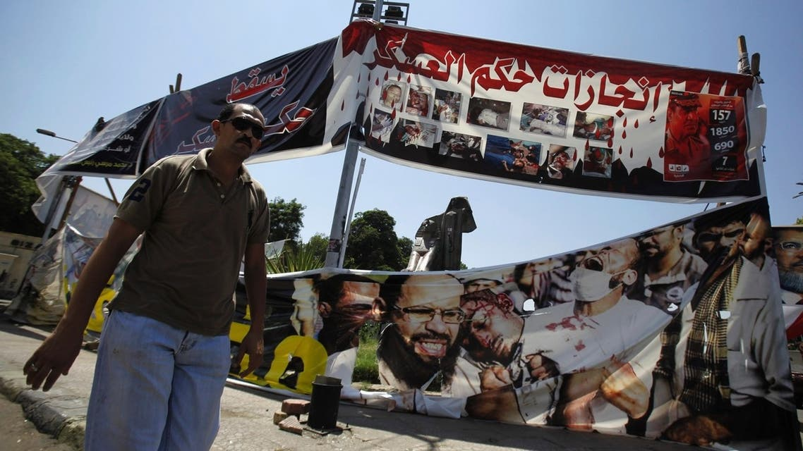 A man walks in front of banners against Egypt's army in front of Nahdet Misr Square and Cairo University, where Mursi supporters are camping