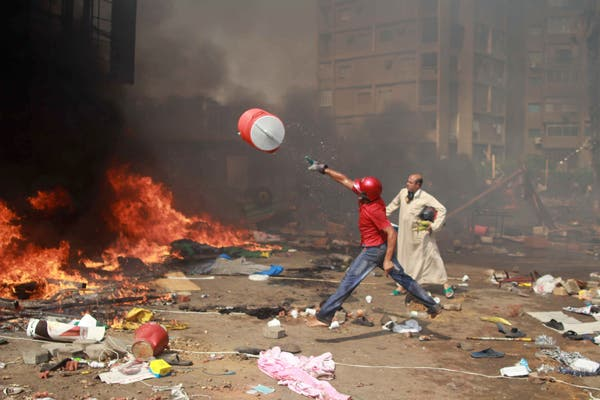 A supporter of the Muslim Brotherhood and Egypt's ousted president Mohamed Morsi throws a water container onto a fire during clashes with police in Cairo. (AFP)