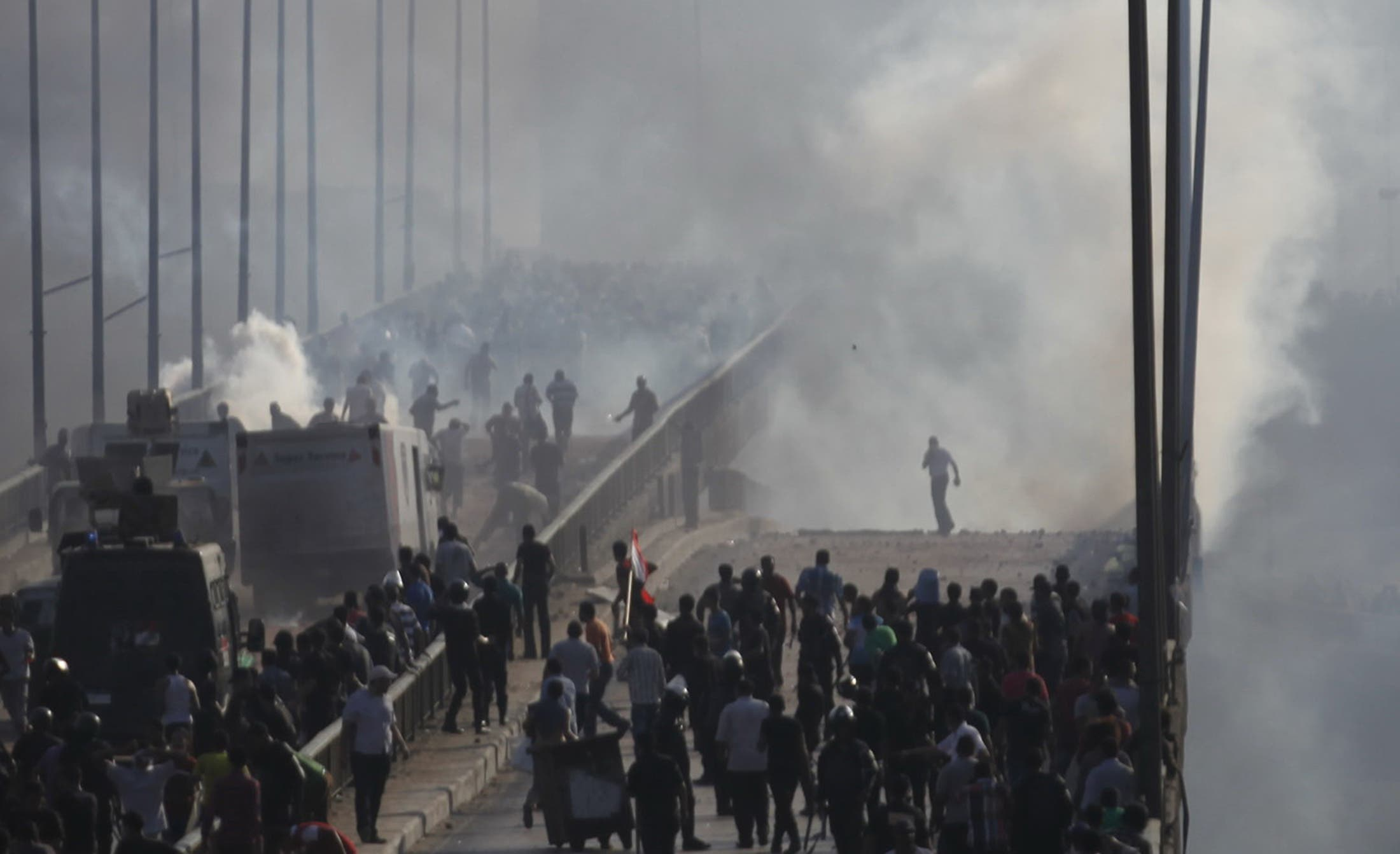 Members of the Muslim Brotherhood flee from tear gas and rubber bullets fired by riot police during clashes, on a bridge leading to Rabba el Adwia Square where they are camping, in Cairo August 14, 2013. (Reuters)