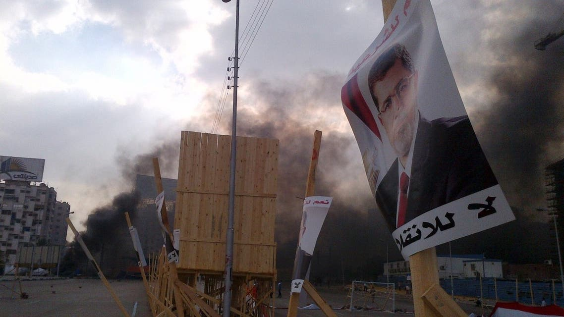 A poster of deposed Islamist President Mohamed Mursi is pictured in front of rising smoke during clashes between riot police and members and supporters of the Muslim Brotherhood, at Rabba el Adwia Square in Cairo August 14, 2013.