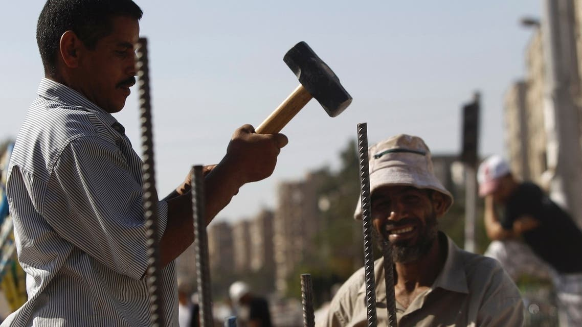 Muslim Brotherhood supporters build a wall with rebars and cement for protection against any attack, at the entrance to their camp at Rabaa Adawiya Square, east of Cairo August 11, 2013. (Reuters)