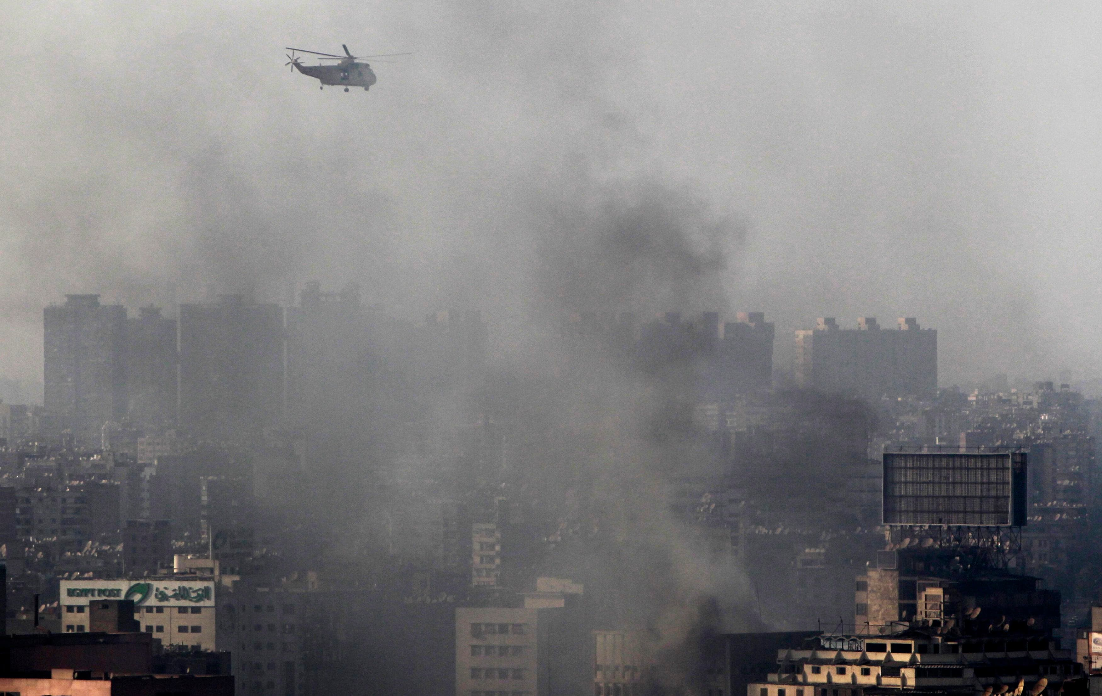 A military helicopter flies over clouds of smoke after clashes between members of the Muslim Brotherhood and supporters of ousted Egyptian President Mohamed Mursi at Azbkya police station during clashes at Ramses Square in Cairo, August 16, 2013. (AFP)
