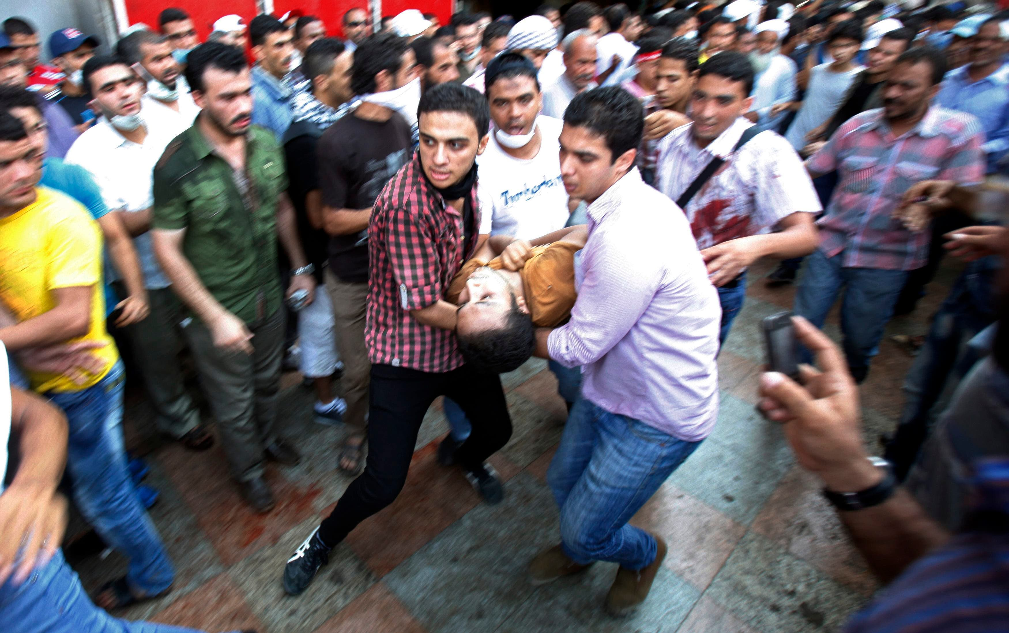 Supporters of deposed Egyptian President Mohamed Mursi carry an injured demonstrator who was shot during clashes in front Azbkya police station at Ramses Square in Cairo, August 16, 2013. (Reuters)