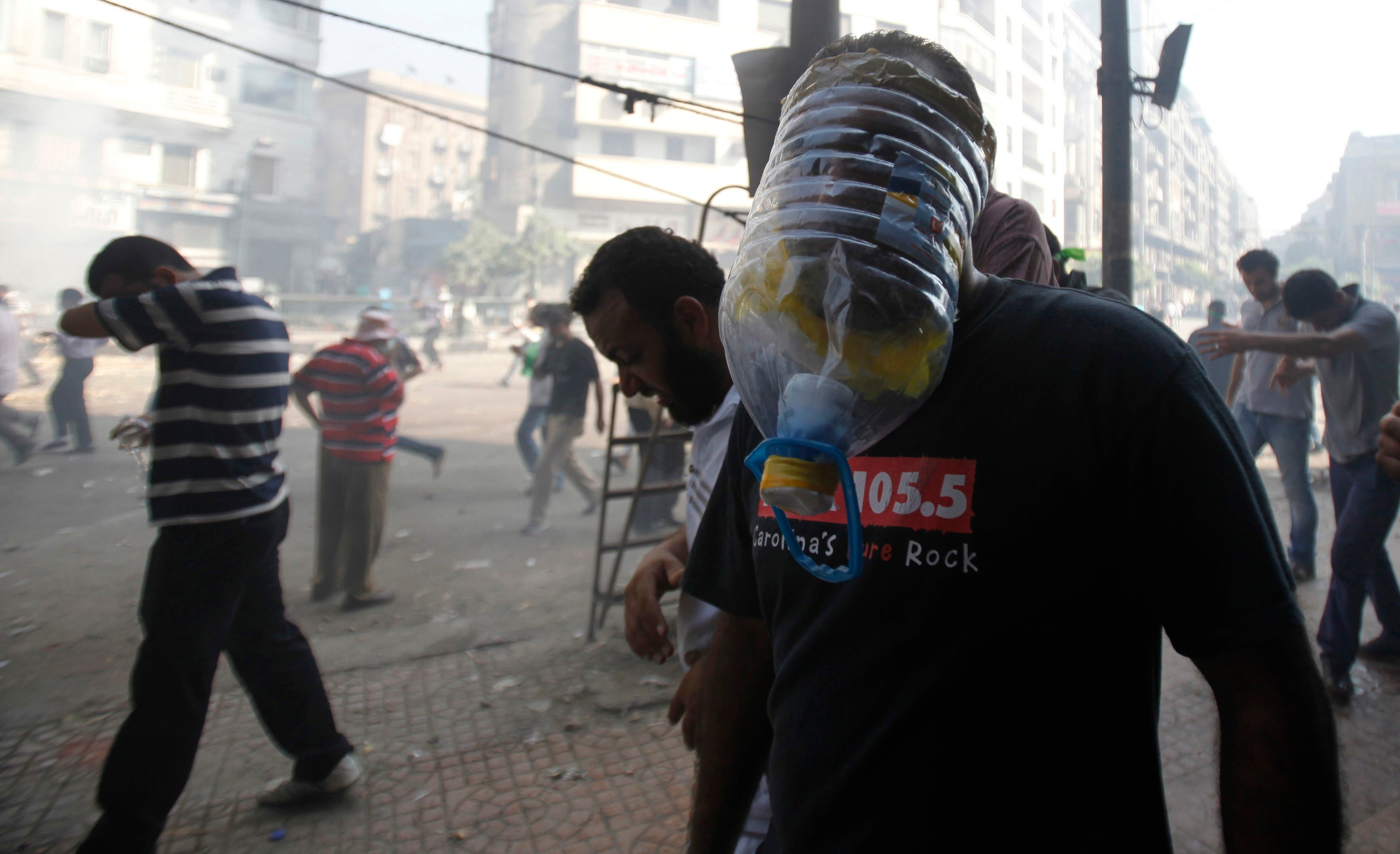 A member of the Muslim Brotherhood and supporter of ousted Egyptian President Mohamed Mursi wears a makeshift gas mask as others run away from shooting during clashes in front of Azbkya police station during clashes at Ramses Square in Cairo August 16, 2013. (Reuters)