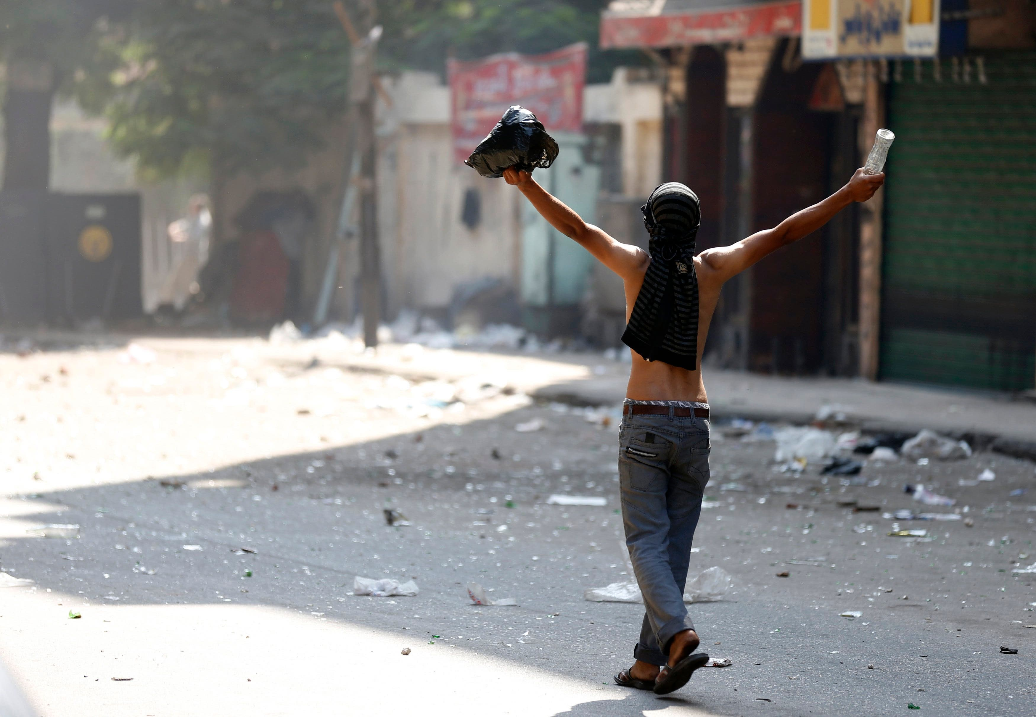 A supporter of ousted Egyptian President Mohamed Mursi gestures during clashes with opponents outside Azbkya police station near Ramses Square in Cairo, August 16, 2013. (AFP)