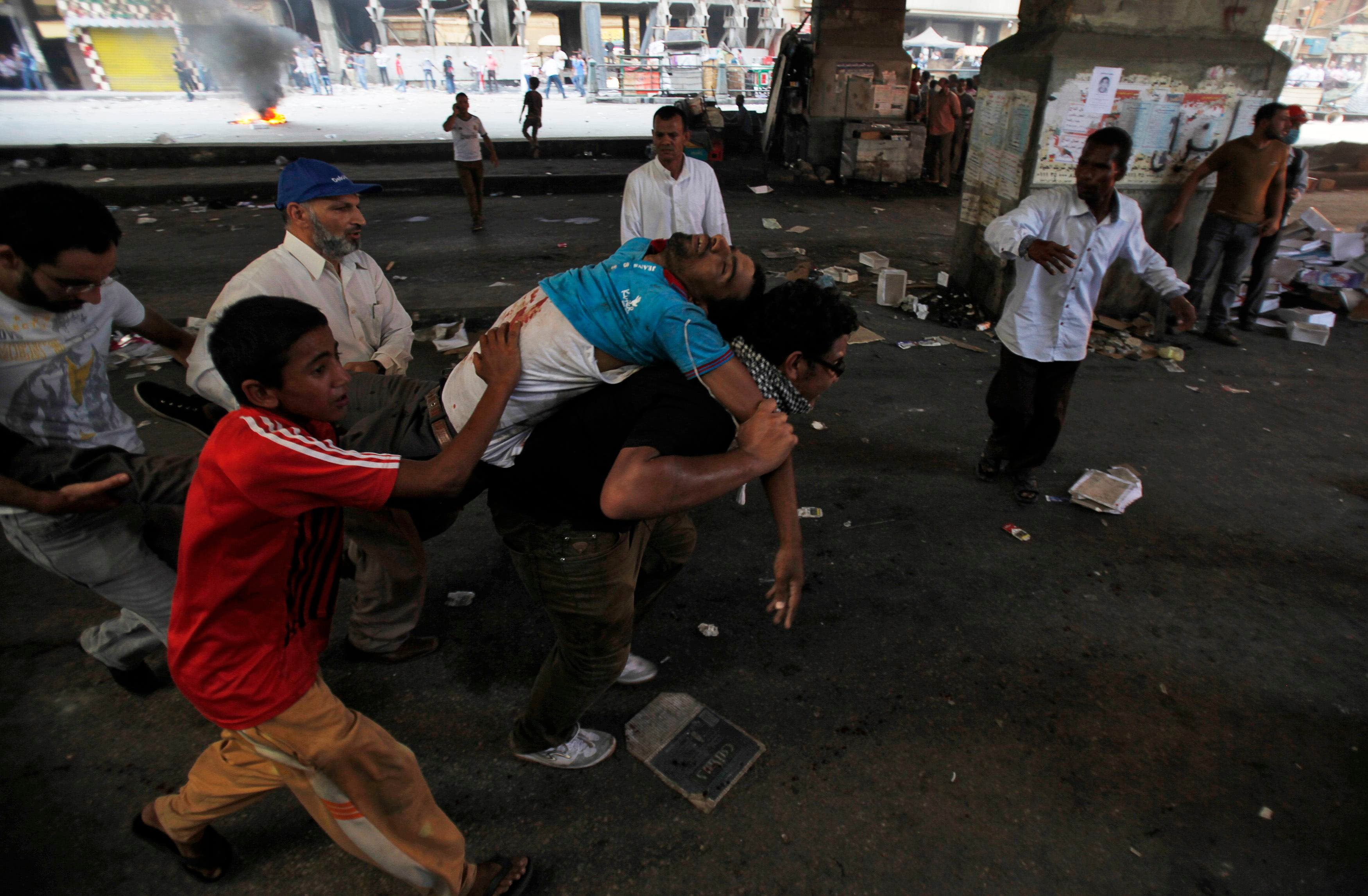 Supporters of deposed Egyptian President Mohamed Mursi carry an injured demonstrator who was shot during clashes in front Azbkya police station at Ramses Square in Cairo, August 16, 2013. (AFP)