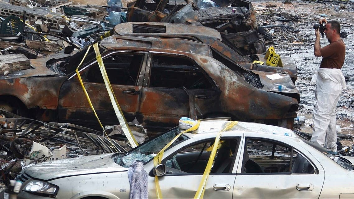 A forensic inspector takes pictures at the site of a car bomb that occurred on Thursday in Beirut's southern suburbs, August 16, 2013.
