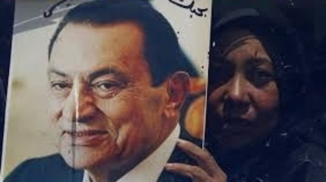 A supporter of Egypt's former president Hosni Mubarak holds a picture of him on a bus after Mubarak's trial, outside the police academy in Cairo April 13, 2013. reuters