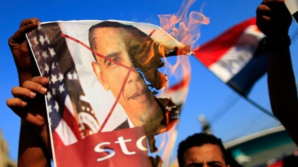 Opponents of Egypt's deposed President Mohamed Mursi burn pictures of U.S. President Barack Obama at a rally in Cairo on July 7