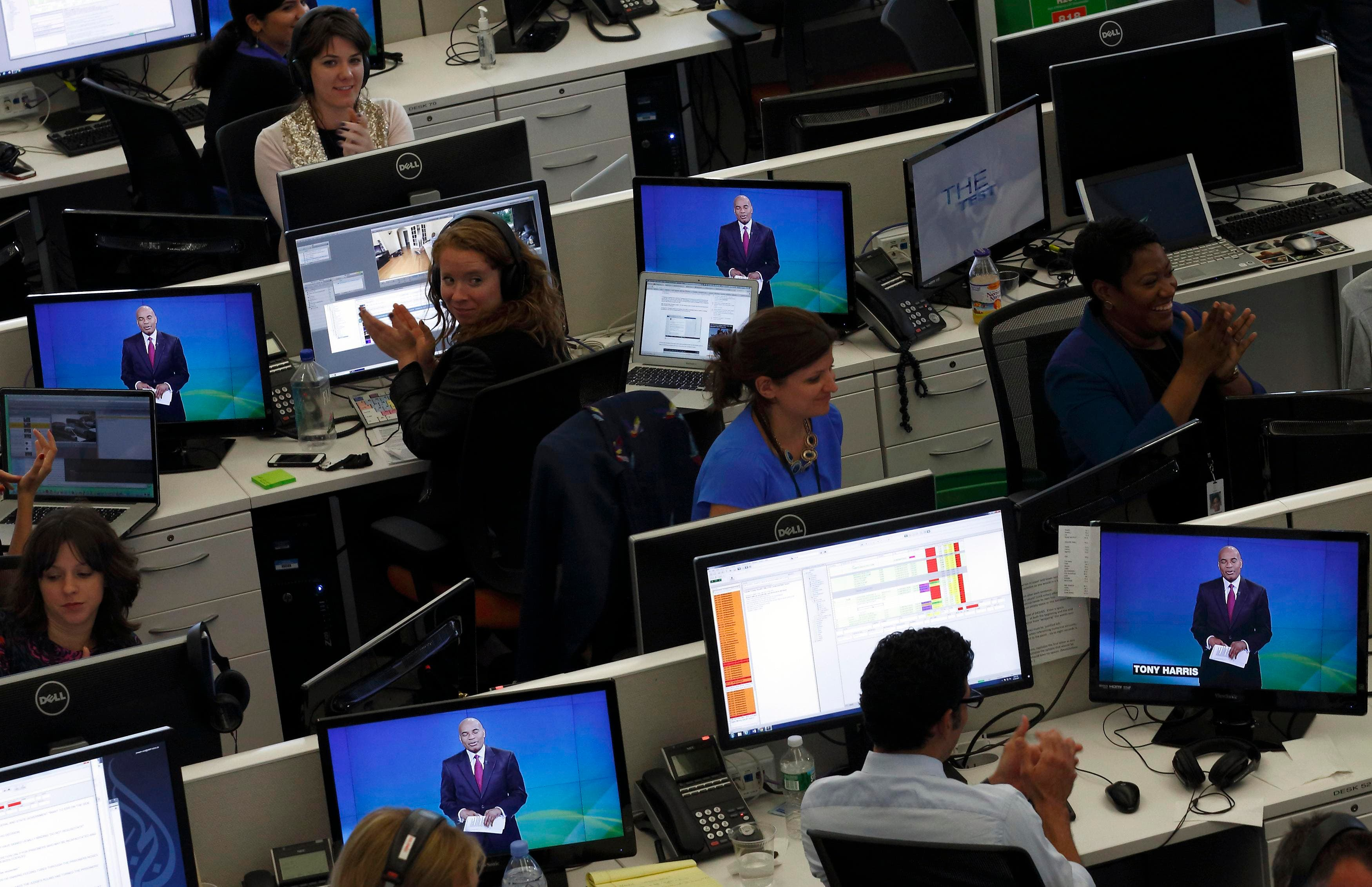 Journalists applaud in the newsroom as Al Jazeera America begins broadcasting in New York, August 20, 2013. (Reuters)