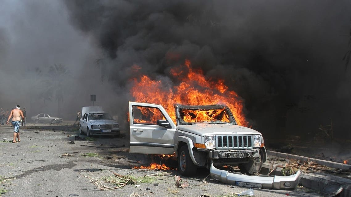 A car burns outside one of two mosques hit by explosions in Lebanon's northern city of Tripoli, August 23, 2013.
