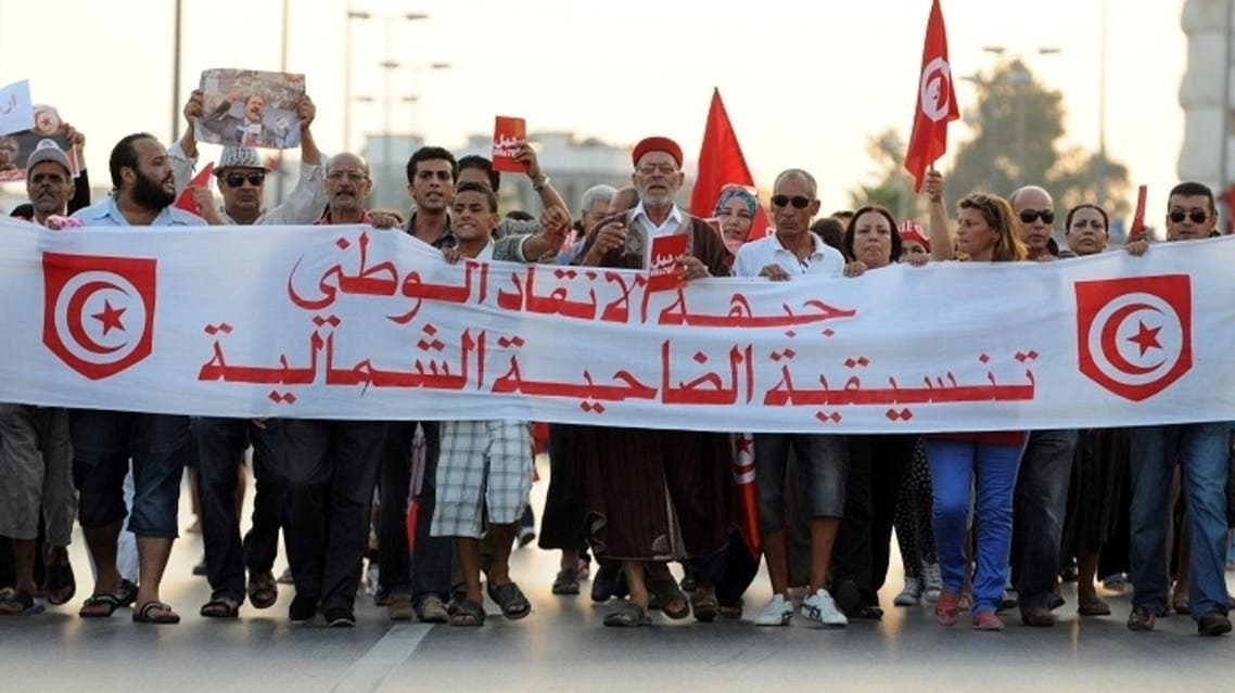 Tunisian demonstrators march during a protest against the country's Islamist-led government in Tunis on August 24, 2013, on the first day of a planned week-long campaign aimed at bringing down the government, amid political deadlock in the country. (AFP)