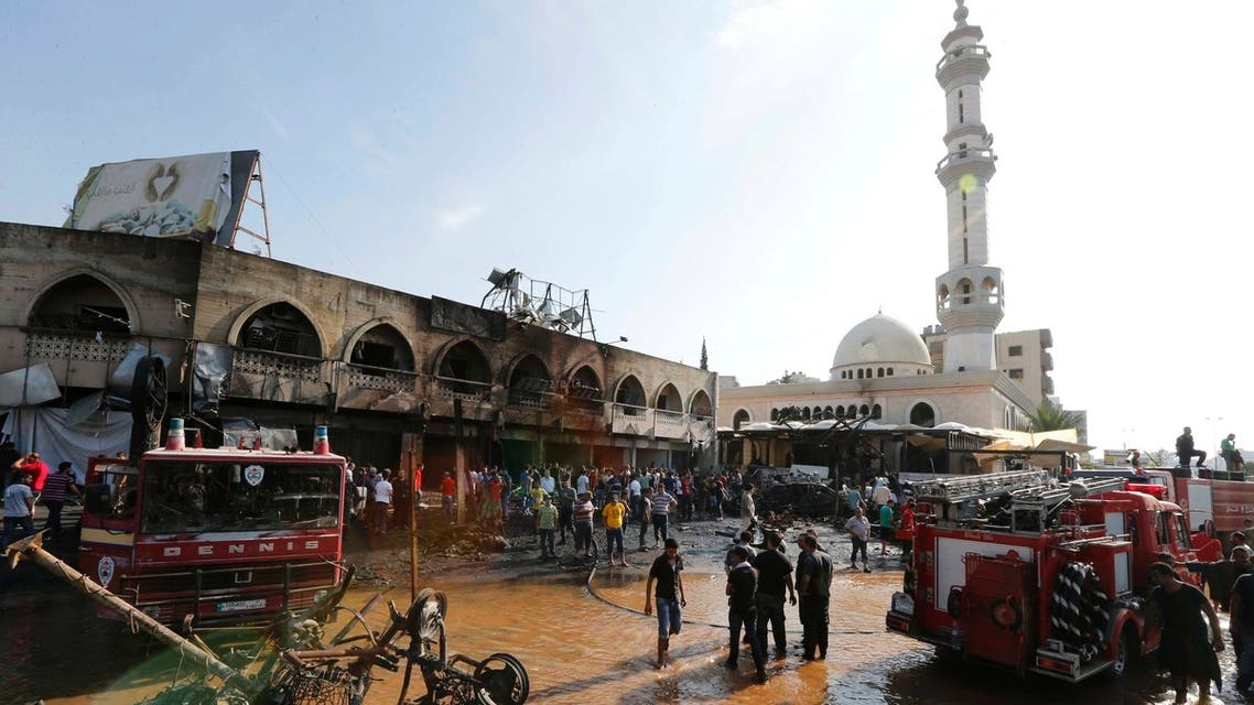 Civil Defence members and residents gather at the site of one of two mosques hit by explosions in Lebanon's northern city of Tripoli, August 23, 2013.