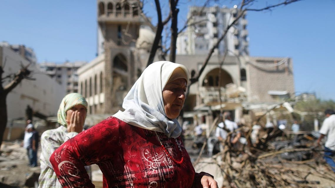 Two women react as they pass by the bomb explosion site in front of al-Salam mosque in the port city of Tripoli in northern Lebanon August 24, 2013.