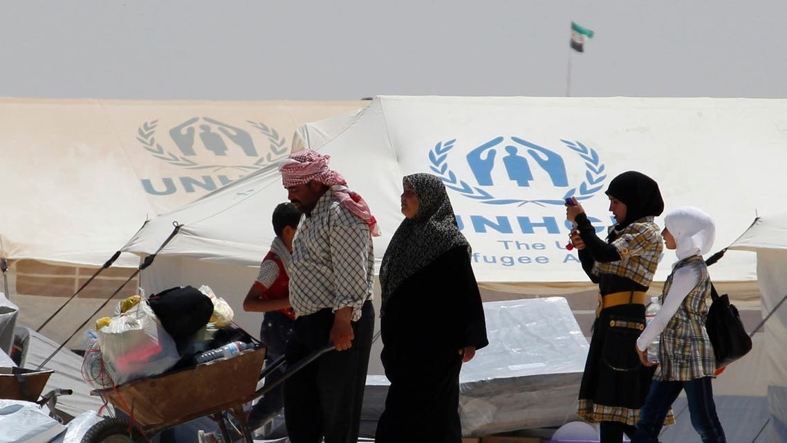 A newly arrived Syrian refugee receives aid and rations, at Al-Zaatri refugee camp in the Jordanian city of Mafraq, near the border with Syria, on World Refugee Day, June 20, 2013. Reu