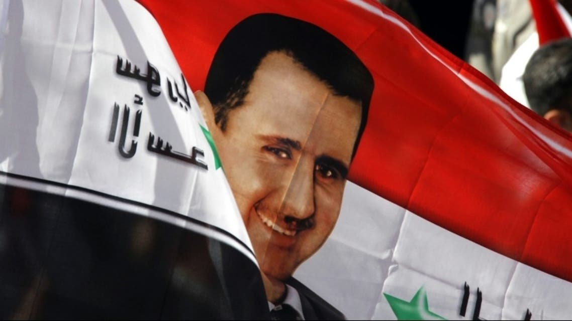 Syrians wave a flag with an image of President Bashar al-Assad during a rally in his support in Damascus. Photograph: Louai Beshara/AFP/Getty Images