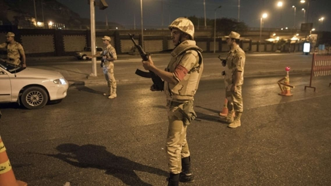 Egyptian troops keep watch at a checkpoint during the curfew hours in Cairo late on August 19, 2013. (AFP)