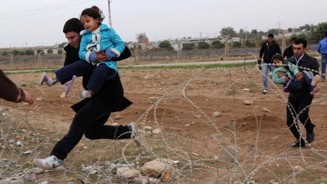 Syrians jump over barbed wire as they flee from the Syrian town of Ras al-Ain to the Turkish border town of Ceylanpinar, Sanliurfa province in this November 9, 2012 file photograph. (Reuters)