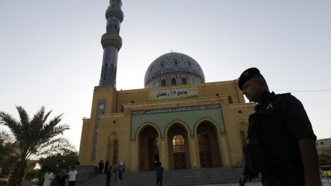 An Iraqi policeman stands guard outside a Sunni mosque during Eid al-Fitr prayers in Baghdad, Aug. 8, 2013. (Reuters)