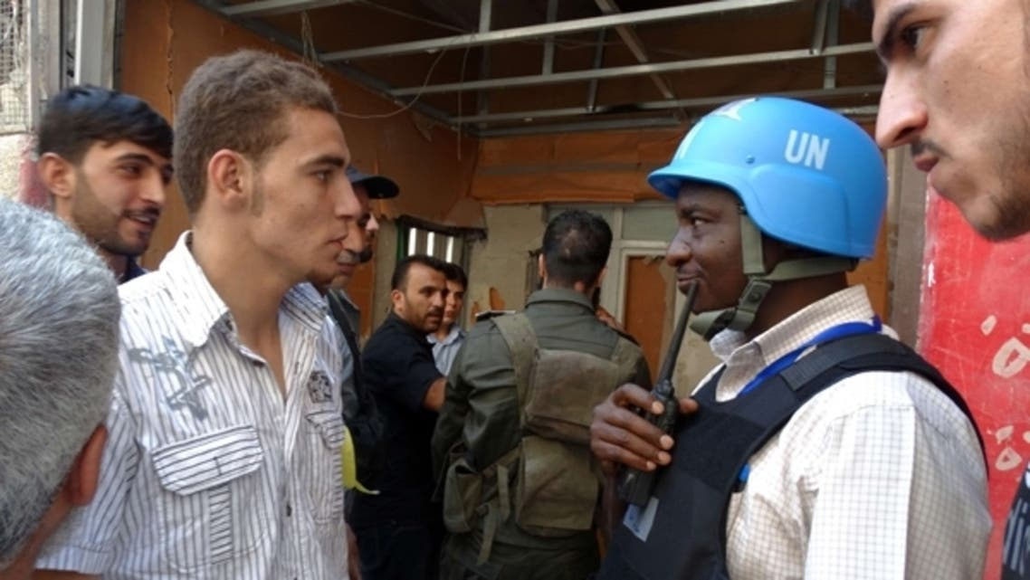 A United Nations (U.N.) arms expert speaks with civilians as they inspect the site where rockets had fallen in Damascus' eastern Ghouta suburb on August 28, 2013, during an investigation into a suspected chemical weapons strike. (AFP)