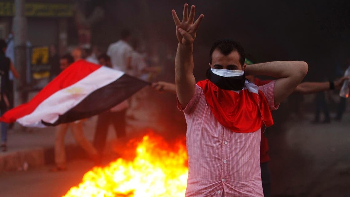 "A supporter of ousted Egyptian President Mohamed Mursi makes the ""Rabaa"" or ""Four"" gesture during clashes at Mohandiseen in Cairo August 30, 2013."