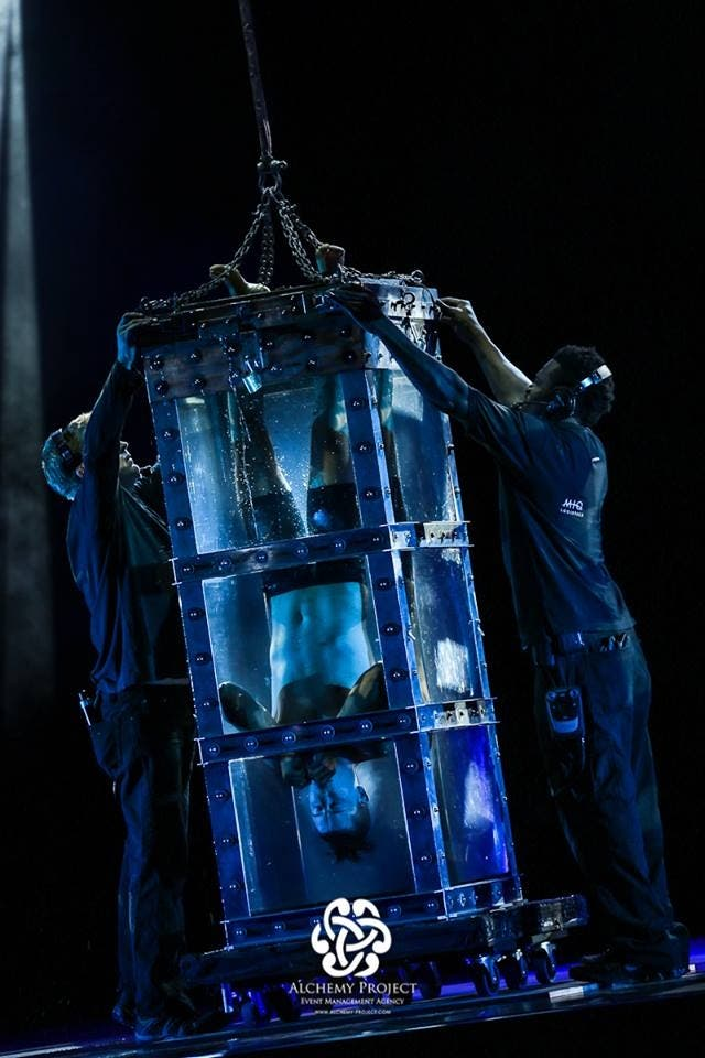 """Andrew Basso, The Escapologist, performed the """"water torture cell"""" act live on stage. (Photo courtesy: Alchemy Project)"""