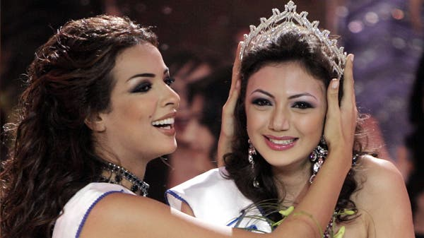 The former Miss Lebanon Nadine Njeim (L) turns over the crown to Gabrielle Bou Rashed, the newly crowned Miss Lebanon 2005, in Beirut December 10, 2005. (Reuters)