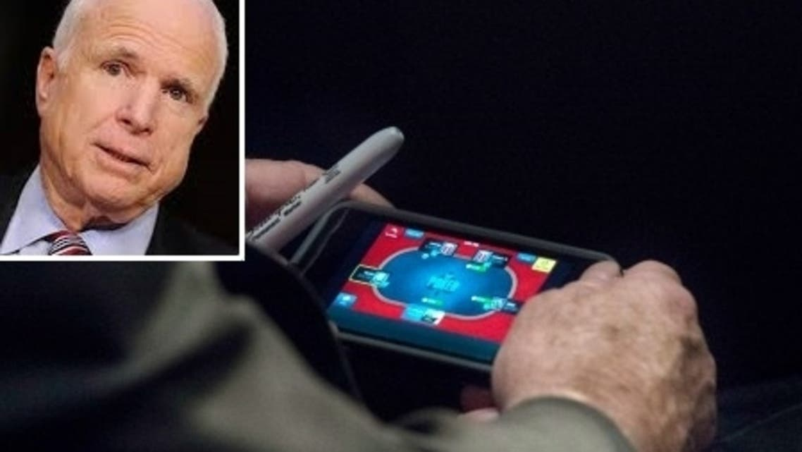 McCain was snapped playing poker on his smartphone. (Washington Post)