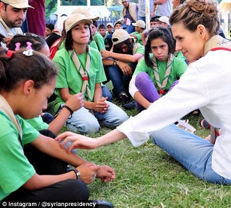 British-born Asma al-Assad reaches out to an unhappy young girl on August 11. (Photo courtesy: Instagram)
