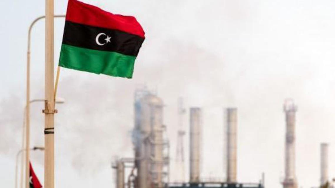 The Libyan flag flutters outside an oil refinery in Zawiya. (File photo: AFP)