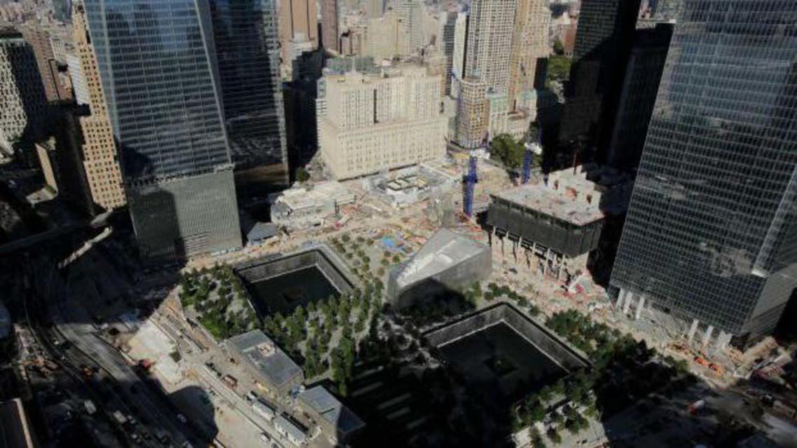 In this photo taken Thursday, Sept. 5, 2013, the wedge-shaped pavilion entrance of the National September 11 Museum, center, is located between the square outlines of the memorial waterfalls at the World Trade Center in New York.