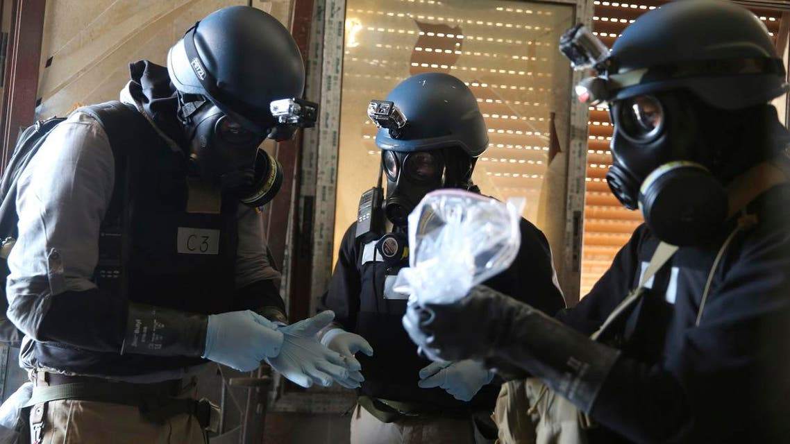 A U.N. chemical weapons expert, wearing a gas mask, holds a plastic bag containing samples from one of the sites of an alleged chemical weapons attack in the Ain Tarma neighbourhood of Damascus August 29, 2013. reuters