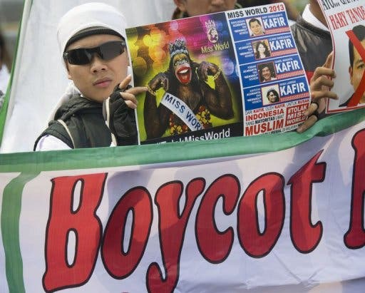 A Muslim protester holds a poster during an anti-Miss World protest in Jakarta on September 6, 2013. (AFP)