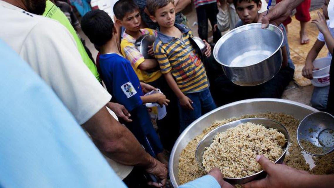 لاجئون سوريون يتلقون مساعدات غذائية