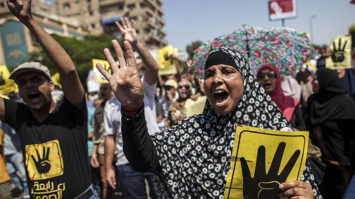 Supporters of ousted Egyptian president Mohamed Morsi raise up posters with the four finger symbol during a demonstration against the military backed government in the Egyptian capital Cairo, on September 13, 2013. afp