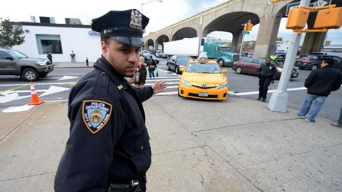 شرطي أميركي يقف أمام محطة الوقود لتنظيم الدخول